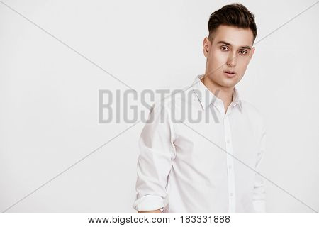 Portrait of a handsome young man in white shirt over white background. Men's beauty, fashion. Businessman. Copy space.