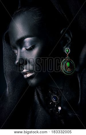 Beautiful young woman with perfect black skin and silver glitter lips wearing beautiful necklace, earrings and black veil. Cosmetics and make-up. Jewelry and bijouterie.