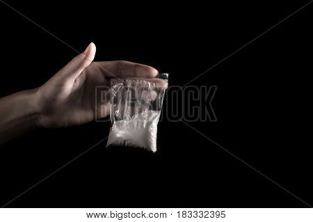packet with white narcotic in hand on black background