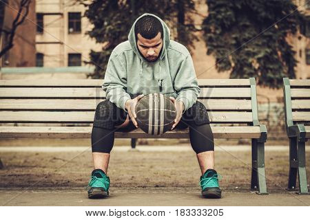 African-american streetball player resting outdoors