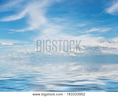 Panorama of vast blue summer sky with fluffy white cumulus and cirrus clouds reflected in a water surface with small waves