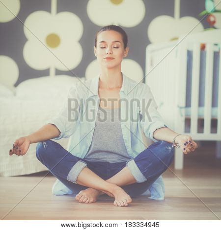Young woman sitting on the floor near children's cot
