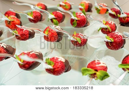 Dessert in chocolate cup filled with cream and strawberry