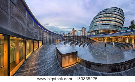 LONDON UNITED KINGDOM - OCTOBER 7 2014: London City Hall and Tower Bridge in London UK. The City Hall has an unusual bulbous shape was designed by Norman Foster and opened in July 2002.