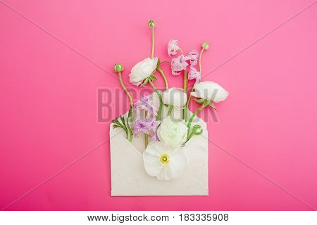 Beautiful flowers and paper envelope on pink background. Flat lay, top view. Flowers background.