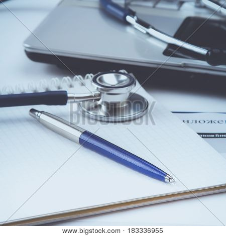 Stethoscope with clipboard and laptop on the desk.