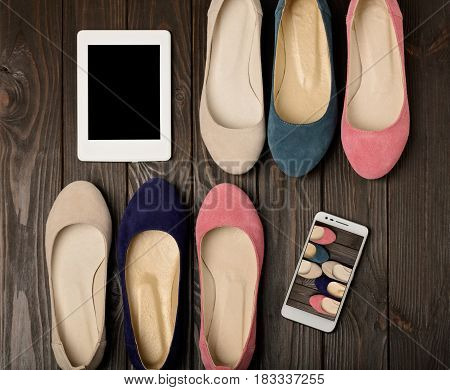 Women's shoes (ballerinas) pink blue and beige on a dark wooden background and smartphone with eBook. Selective focus.