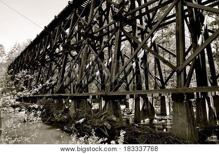 Abandoned railroad bridge and trestles with a river flowing underneath (black and white)