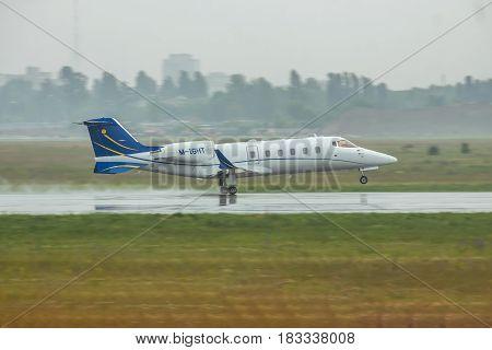 Kiev Ukraine - June 5 2012: Bombardier Learjet 60 business jet is taking off in heavy rain