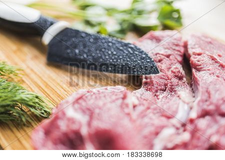 Fresh red beef meat, bright green dill and parsley, a knife with a black wide blade on a light bamboo board. Beautiful and healthy cooking concept.