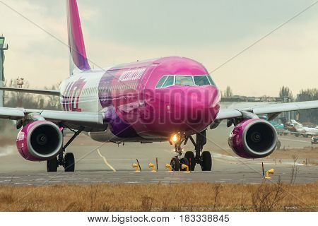 Kiev Ukraine - December 24 2012: WizzAir Airbus A320 passenger plane is taxiing to the runway on a cold winter day