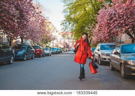 happy young women walking after shopping by street blooming with sakura