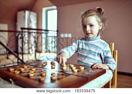 Little funny girl , playing checkers .