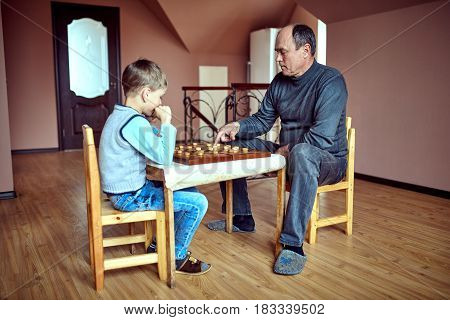 Caucasian grandfather and grandson playing checkers .