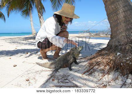 Woman cuddle Cuban rock iguana on the tropical beach