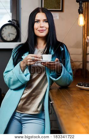 Young woman resting with coffee in cafe