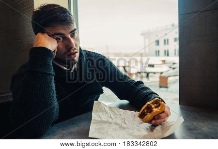 a young man dressed in black and with a beard sitting in a restaurant and can no longer eat up your burger