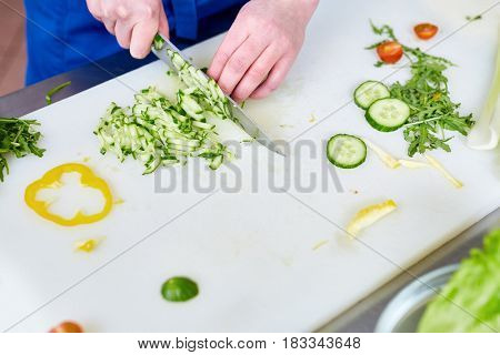 Hands of young trainee with knife cutting fresh cucumbers
