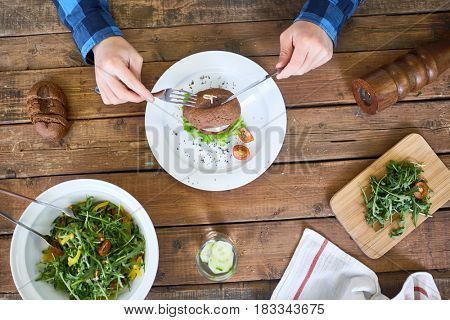 Human hands with fork and knife during lunch