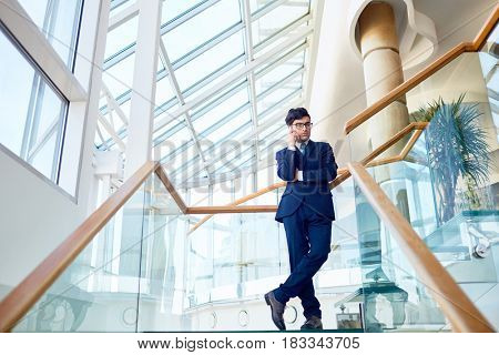 Young agent talking on cellphone inside modern building
