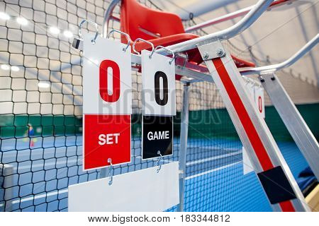 Umpire chair with scoreboard on a tennis court before the game. The playground is empty and the score is zero to zero.