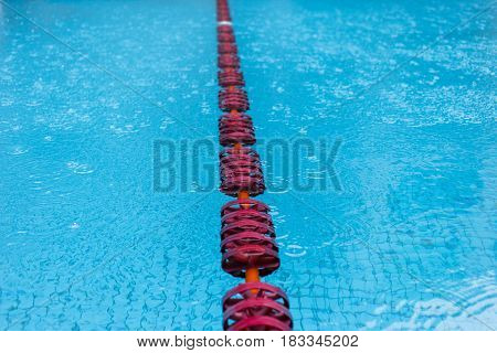 Swimming pool with red floats and clear blue water