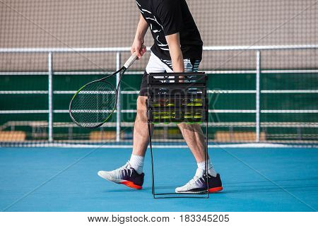 The legs of man in a closed tennis court with ball and racket