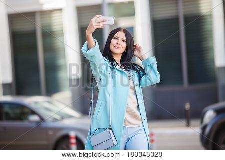 Beautiful brunette taking picture of herself on street near building