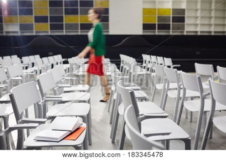 Businesswoman moving in aisle of conference hall between chairs