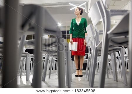 Young teacher with notepad standing inside lecture hall