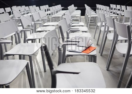 Open notebook on one of chairs in conference hall
