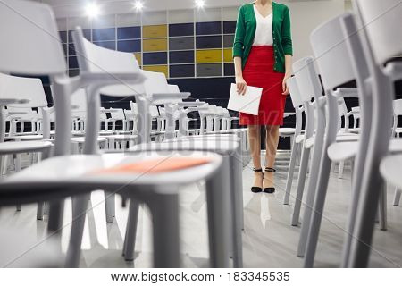 Young female with notepad standing by row of chairs in conference hall