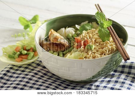 instant noodles in bowl with Thai herb on wood background