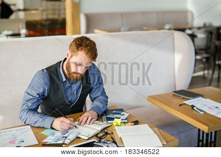 Businessman concentrating on writing financial analysis in notebook