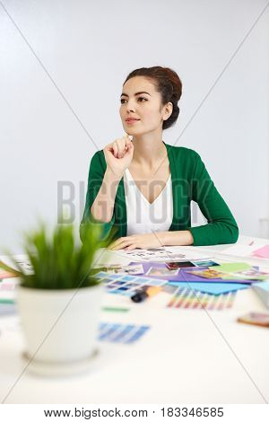 Pensive designer thinking of new ideas by workplace