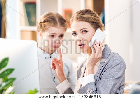 Young Mother And Daughter Talking In Business Office, Businesswoman Using Smartphone