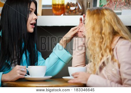 Two girlfriends chatting in cafe for mug of tea
