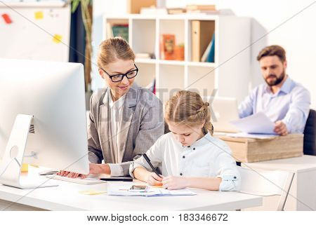 Young Mother Working While Her Daughter Drawing In Business Office, Father Behind