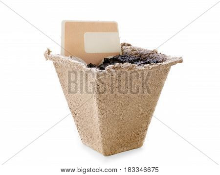 Small peat pot filled by soil with blank label. Copy space on the label. Isolated on white clipping path included