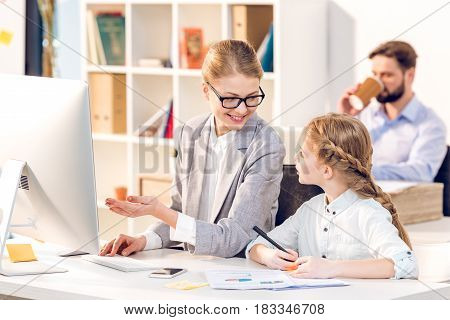 Young Mother And Daughter Talking In Business Office, Father Behind