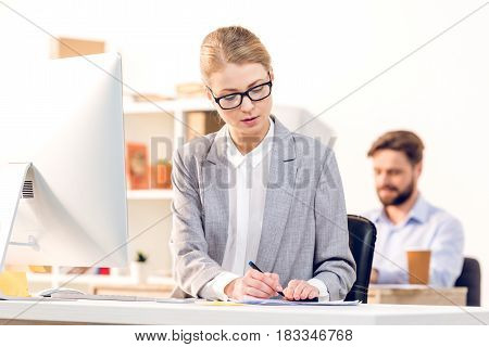 Attractive Businesswoman With Eyeglasses Using Computer Working In Office, Colleague Behind