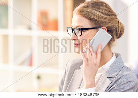 Attractive Businesswoman With Eyeglasses Using Smartphone Working In Office