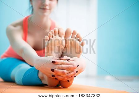 Photo of woman on sports rug practicing yoga in gym