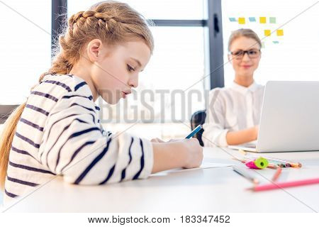 Adorable Daughter Drawing, Businesswoman Working With Laptop Behind In Office