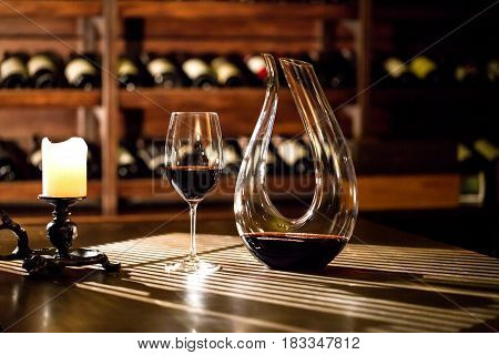 Wine glass and figured wine bottle placed on a table in a wine vault.