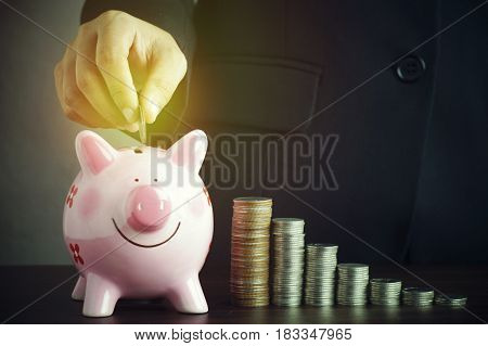 hand put money on piggy bank and pile of coins