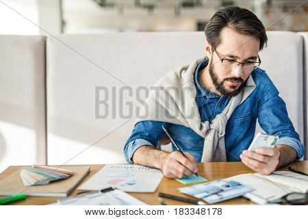 Serious economist with smartphone searching for data in the net