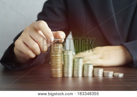 hand put money on pile of coins , concept in account and finance growing up step by step