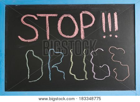 Conceptual stop sign narcotics colored chalk on a slate with a blue frame
