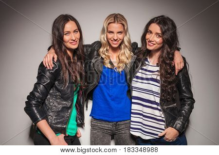 smiling blonde woman embracing her friends against grey studio wall